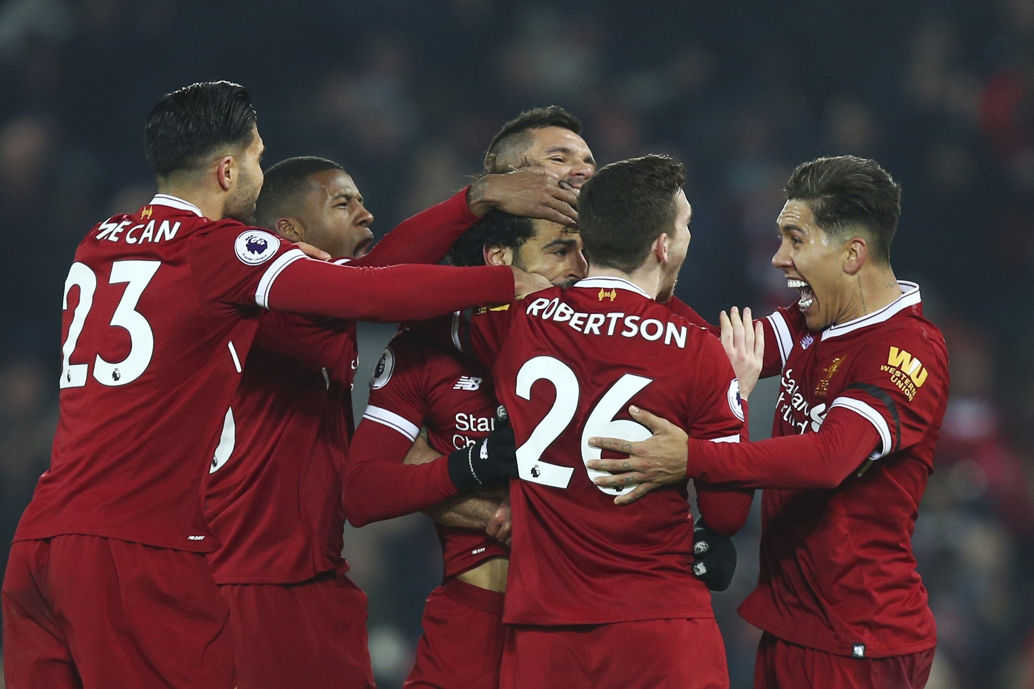 Liverpool players celebrate with Mohamed Salah, center, after he scored his side's fourth goal during the match between Liverpool and Manchester City. (AP Photo)