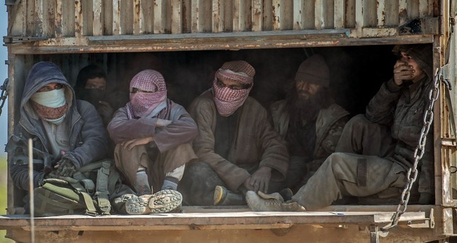 In this Feb. 20, 2019 photo, a truck carrying men, identified as Daesh fighters who surrendered to the U.S.-backed SDF, consisting mainly for PKK-affiliated YPG terrorists, transports them out of Baghouz in Deir el-Zour province, Syria. AFP Photo