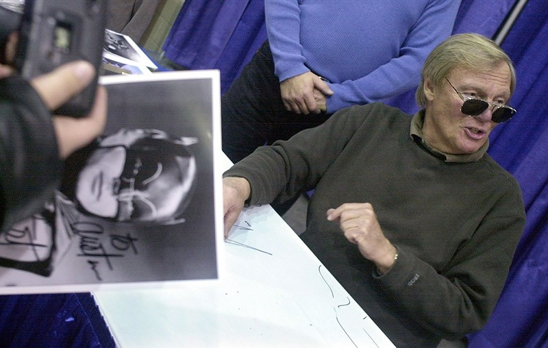 In this Feb. 23, 2002 file photo, a fan holds a signed photograph of actor Adam West, right, during the 50th Autorama in Detroit. (AP Photo)