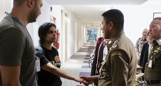 Handout picture released by Thai Immigration Bureau on Jan. 7, 2019, shows 18-year-old Saudi woman Rahaf Mohammed Alqanun (2nd-L) shaking hands with a Thai immigration officer at the Suvarnabhumi international airport in Bangkok. (AFP Photo)