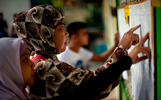 Muslim women look for their names at a voting precinct in Maguindanao, on the southern island of Mindanao on January 21, 2019 (AFP Photo)