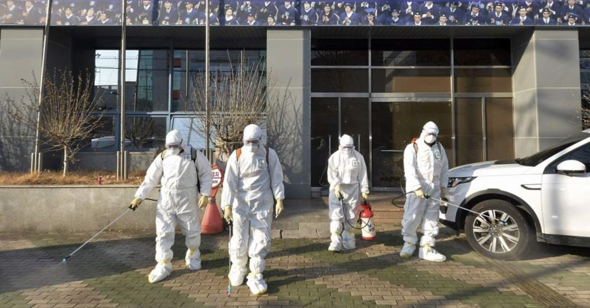 In this Wednesday, Feb. 19, 2020, photo, workers wearing protective gears spray disinfectant against the coronavirus in front of a church in Daegu, South Korea. (Newsis via AP)