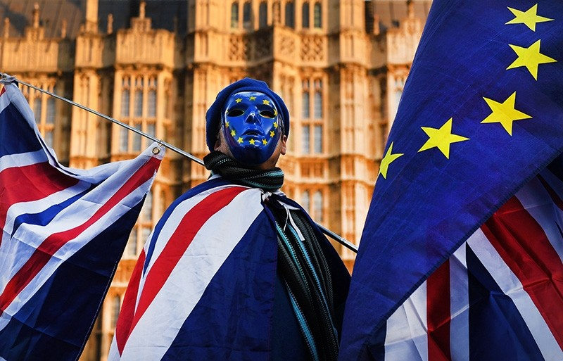 Pro EU protester wearing a mask with EU stars and holding EU and British flags demonstrates outside the Parliament in London (EPA Photo)