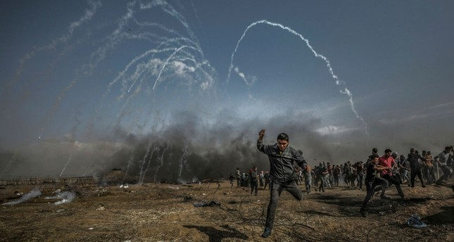 Palestinian protesters run for cover from teargas fired by Israeli soldiers after Friday's protests near the border with Israel, Gaza Strip, April 27.