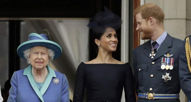 Britain's Queen Elizabeth II, Meghan the Duchess of Sussex and Prince Harry watch a flypast of Royal Air Force aircraft over Buckingham Palace, London, July 10, 2018. AP Photo