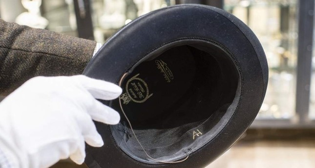 A man holds a hat with the initials of Adolf Hitler prior to an auction in Grasbrunn, Germany, Wednesday, Nov. 201, 2019. AP Photo