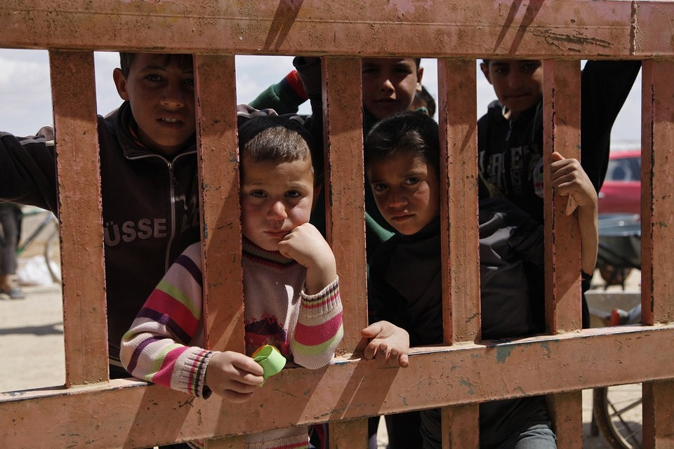 In this April 14, 2016 photo, Syrian refugees look through the gate of a grocery store at the al-Azraq refugee camp in northeast Jordan. (AP Photo)