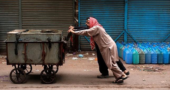 Men push a water tank trolley door to door through the streets of Karachi, Pakistan January 12, 2018. (Reuters Photo)