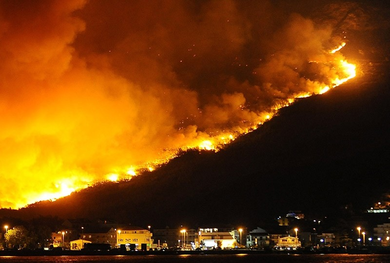Wildfires in the hills illuminate the scenery near a district of the coastal town of Split, Croatia, in the early morning hours of 18 July 2017. (EPA Photo)
