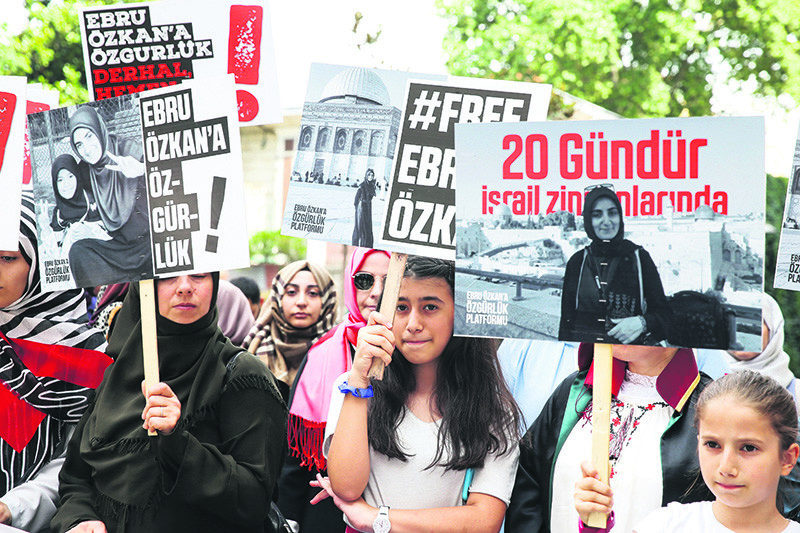 People hold placards with slogans reading ,Free Ebru u00d6zkan, and photos of u00d6zkan during a rally calling for her release in Istanbul on June 30.