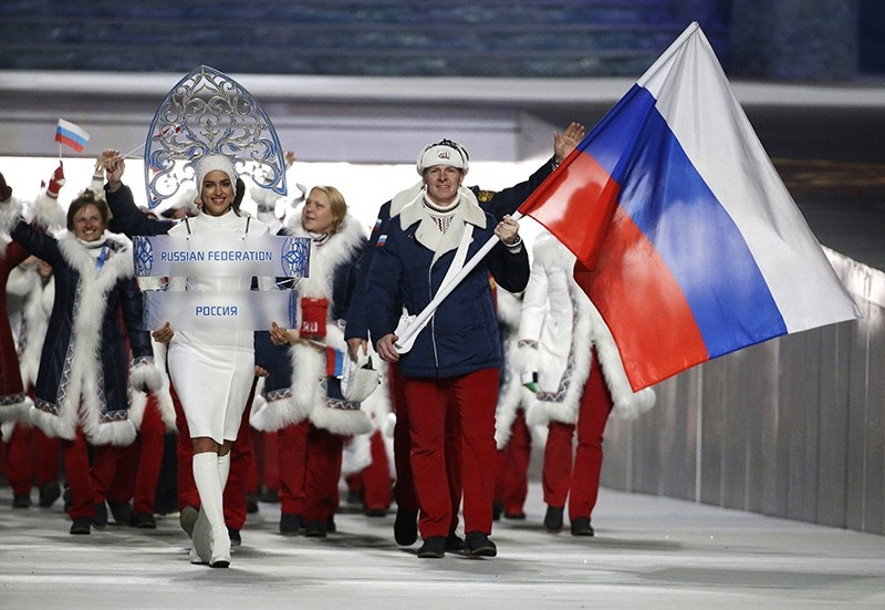 In this Feb. 7, 2014 file photo Alexander Zubkov of Russia carries the national flag as he leads the team during the opening ceremony of the 2014 Winter Olympics in Sochi, Russia. (AP Photo)