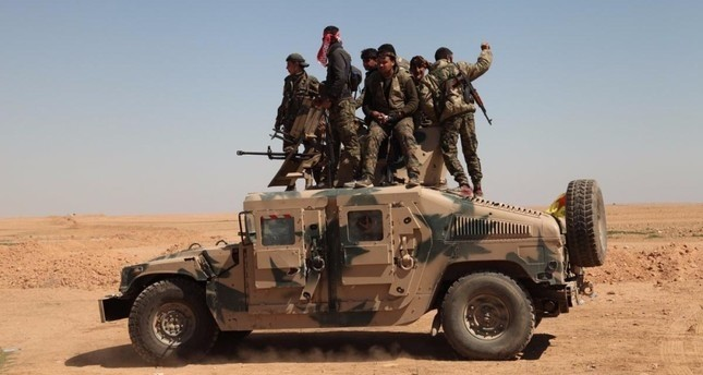 YPG terrorists are seen on the top of a U.S. armored vehicle in the Raqqa operation.