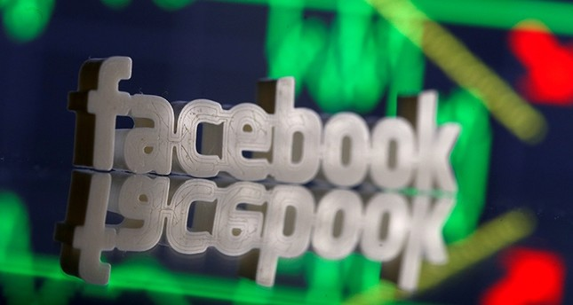 A 3D-printed Facebook logo is seen in front of displayed stock graph in this illustration photo, March 20, 2018. (Reuters Photo)