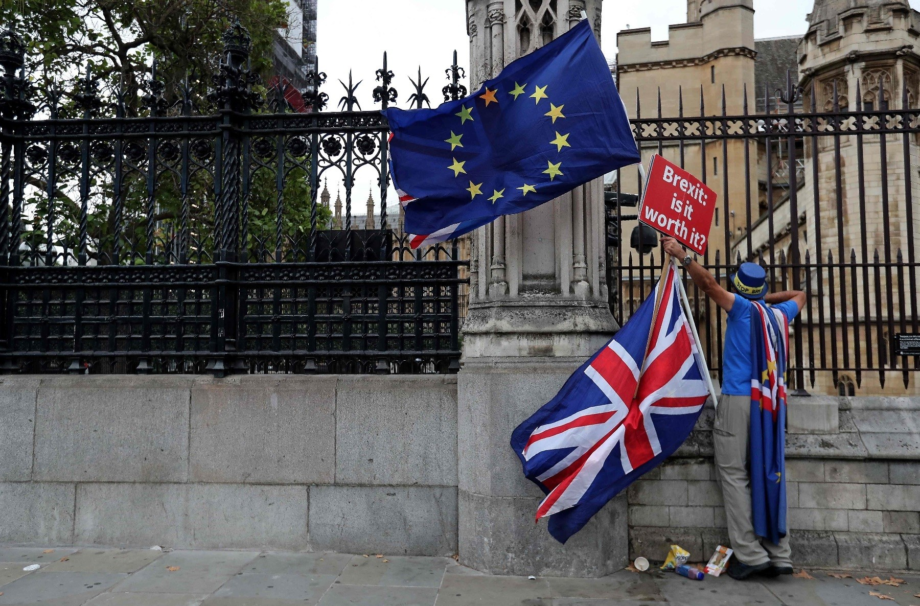 A demonstrator holds a sign that reads ,Brexit: Is it worth it?, while waving an EU flag, as he protests outside the Houses of Parliament in central London, Sept. 11, 2018.