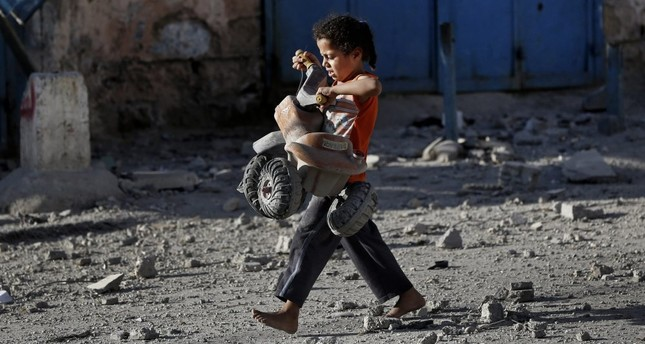A Palestinian girl walks with a toy that she salvaged from the debris of a building, Gaza City, July 17, 2014.