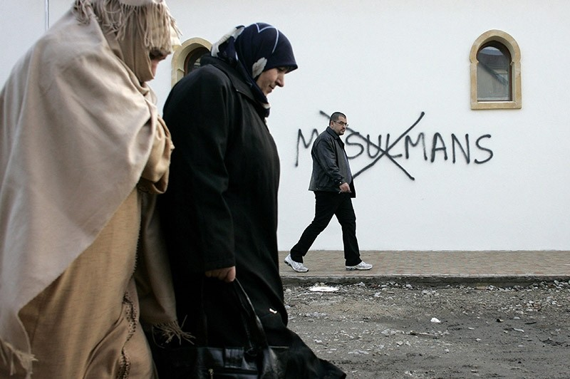 Muslim residents walk past racial slurs painted on the walls of a mosque in the town of Saint-Etienne, central France. (AP File Photo)