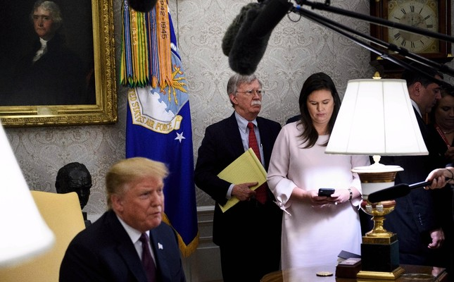 U.S. National Security Advisor John R. Bolton (C), White House Press Secretary Sarah H. Sanders (R) and others listen while U.S. President Donald Trump (L) speaks to the press in the Oval Office of the White House, May 13, 2019.