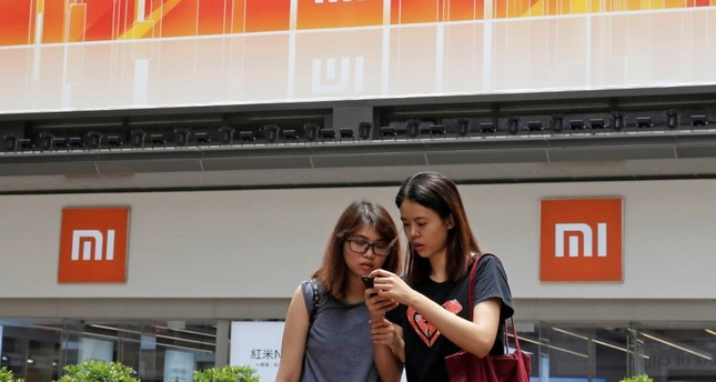 In this Wednesday, June 20, 2018, photo, people use their smartphone outside a Xiaomi store in Hong Kong. (AP Photo)