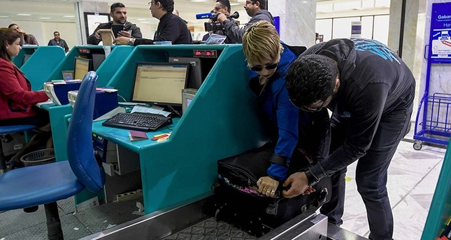 A Tunisian couple bound for London pack away their electronics in their luggage as they check-in for a flight at Tunis-Carthage International Airport on March 25, 2017. (AFP Photo)