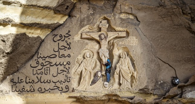 Polish artist Mario, sculptor of St. Simon the Tanner Monastery complex, works on a scene relief depicting the Crucifixion of Jesus Christ and a verse in Arabic from the Biblical Book of Isaiah (AFP Photo)