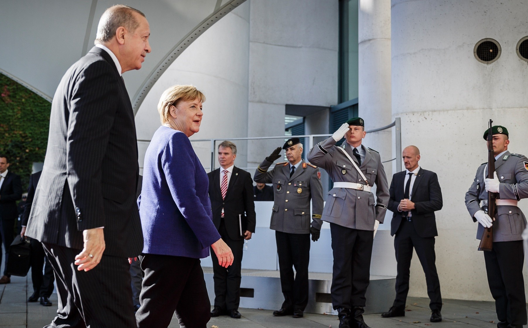 President Erdou011fan (L) and German Chancellor Angela Merkel (2-L) walk to a meeting on the future of bilateral ties at the Chancellery, Berlin, Sept. 29.
