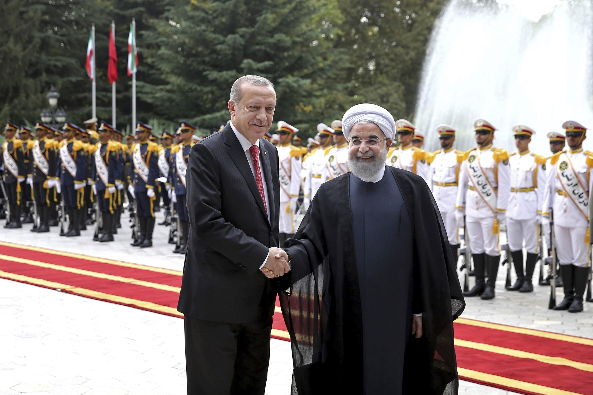 Erdou011fan (L) shakes hands for the cameras with Iranian President Rouhani, during the official arrival ceremony, at the Saadabad Palace in Tehran Oct. 4, 2017. (AP Photo)