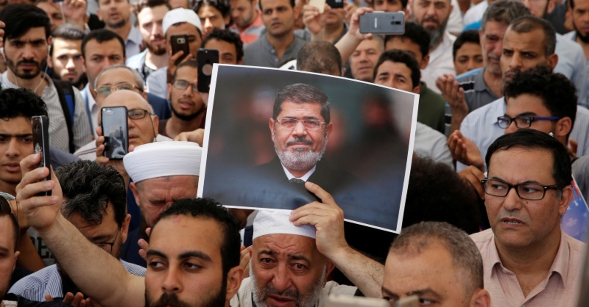 A man holds a picture of the former Egyptian President Mohamed Morsi during a symbolic funeral prayer at the courtyard of Fatih Mosque in Istanbul, Turkey, June 18, 2019. (Reuters Photo)