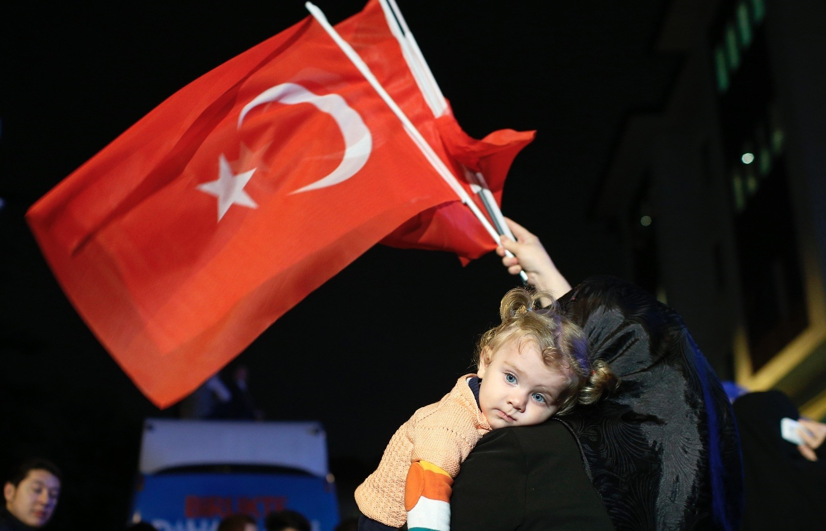 A supporter of Turkeyu2019s ruling Justice and Development Party holds a baby as she waves Turkish flags, u0130stanbul, Turkey, June 7, 2015.