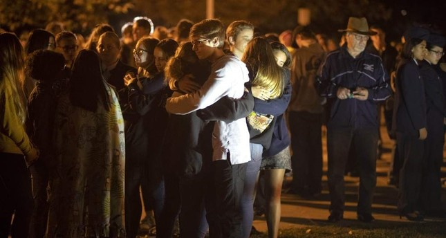 People affected by the Saugus High School shooting comfort each other during a vigil at Central Park in Santa Clarita, California, Thursday, Nov. 14, 2019. Hans Gutknecht/The Orange County Register via AP