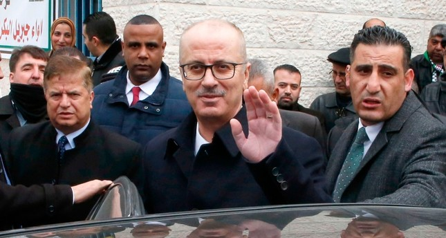Palestinian Prime Minister Rami Hamdallah waves upon his arrival to attend a ceremony marking the opening of a medical center in the village of Beit Ula, north of the West Bank city of Hebron on Jan. 28, 2019. (AFP Photo)