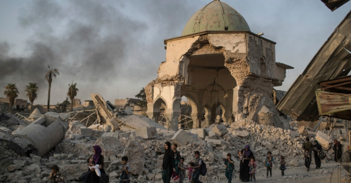 In this July 4, 2017, file photo, fleeing Iraqi civilians walk past the heavily damaged al-Nuri mosque as Iraqi forces continue their advance against Daesh terrorists in Iraq's Old City of Mosul. (AP Photo)