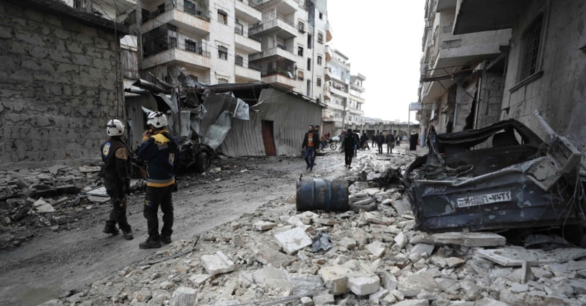 Syrian rescuers known as the White Helmets walk amid the rubble scattered across a street following a reported regime airstrike in the town of Ariha in the Idlib province on Jan. 5, 2020. (AFP Photo)