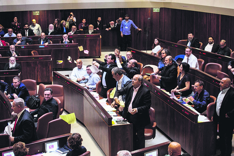 Arab lawmakers stand up in protest during a Knesset session against the parliamentu2019s approving a controversial bill to define Israel as the nation-state of the Jewish people, July 18, 2018. (AP Photo)