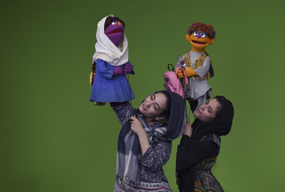 Afghan puppeteer Seema Sultani (R) holds new u201cSesame Streetu201d muppet u201cZeeraku201d as she performs with colleague  Mansoora Shirzad holding u201cZariu201d during a recording at the television studio in Kabul.