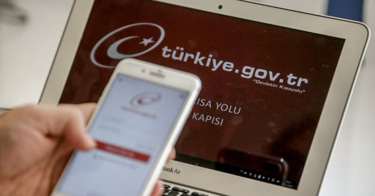 e-Devlet (e-State) login screens on a laptop and cellphone. (AA Photo)