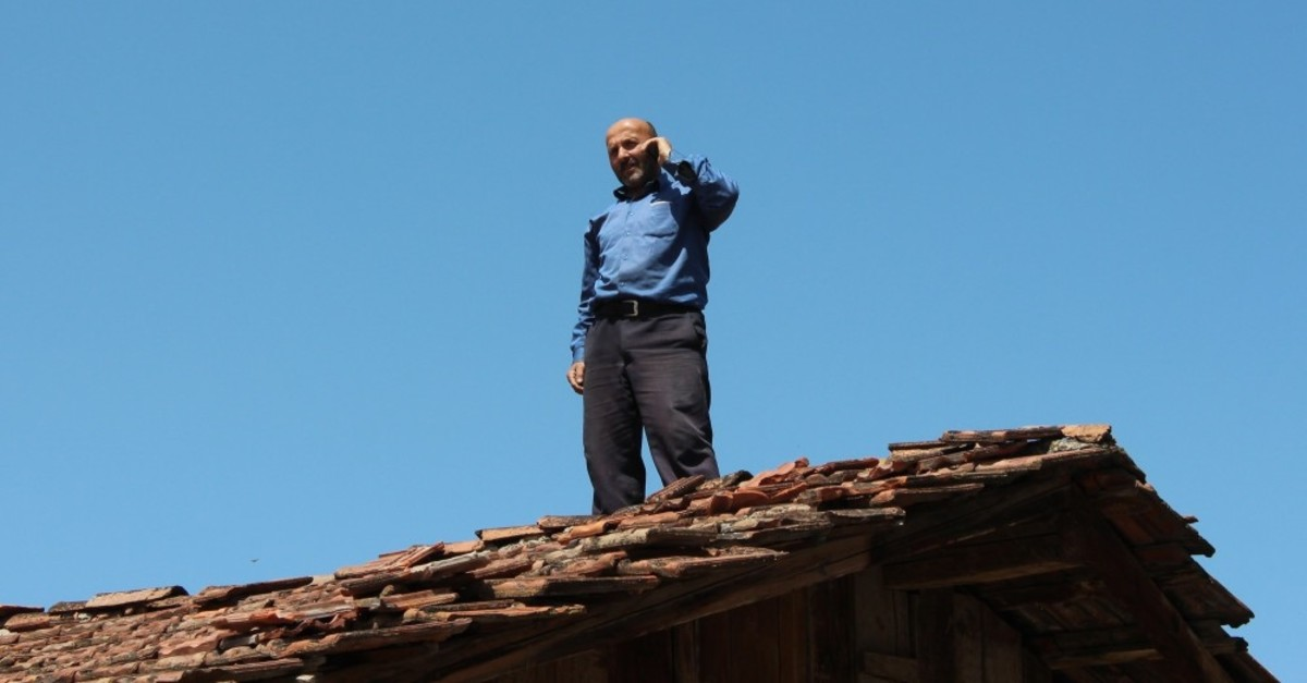 One of the villagers on the roof of a house to get a phone signal.