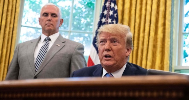 US President Donald Trump speaks to the press before signing a bill for border funding legislationin as Vice President Mike Pence looks on in the Oval Office at the White House in Washington, DC, on July 1, 2019. (AFP Photo)