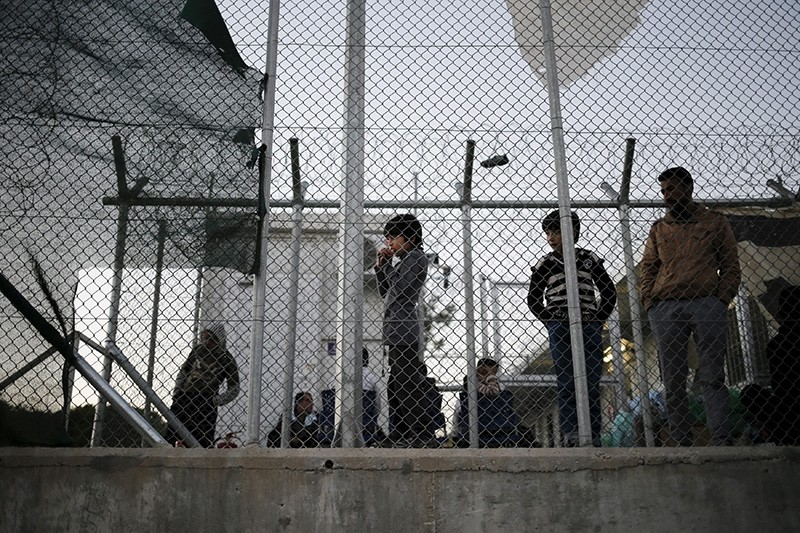 A migrant child stands next to a metal fence at the Moria refugee camp on the Greek island of Lesbos (Reuters File Photo)