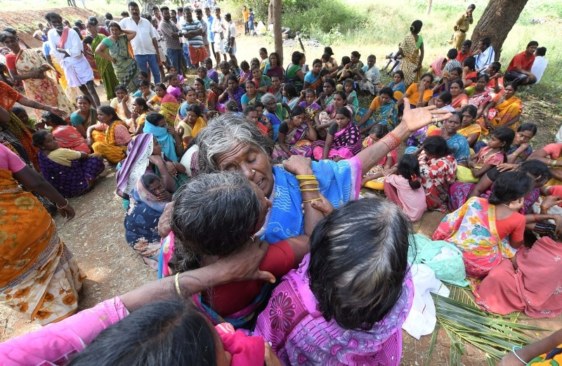 Indian women mourn the death of relatives in a case of suspected food poisoning at Bidarahalli, near Sulawadi village in Chamarajnagar district of Karnataka state, India, Saturday, Dec. 15, 2018. (AP Photo)
