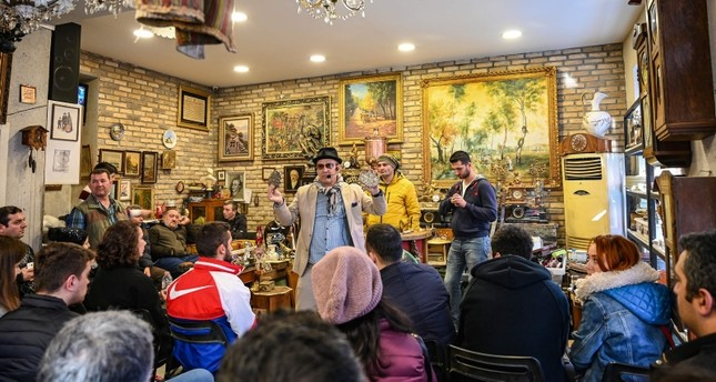 Auctioneer Ali Tuna (C) shows items to the audience at an auction house in Istanbul's Balat district on February 3, 2019. (AFP Photo)