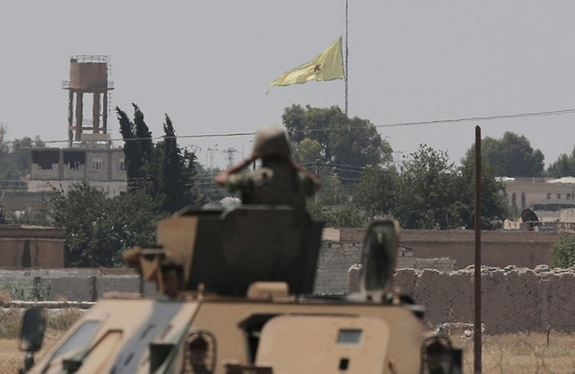 In this photo taken in Akçakale, SE Turkey, a Turkish soldier on an armored personnel carrier watches as in the background a flag of the PKK-linked YPG, is raised across the border over the city of Tal Abyad, Syria, Tuesday, June 16, 2015. (AP Photo)