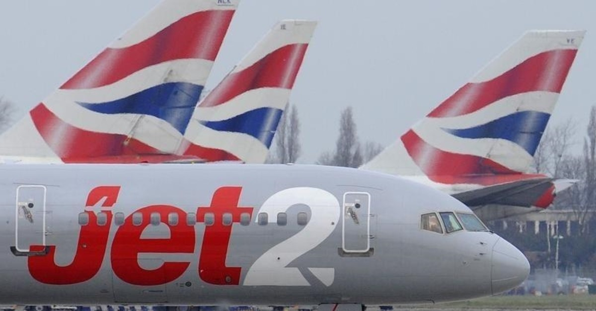 A Jet2 aircraft taxis past British Airways aircraft at Terminal 5 of Heathrow Airport in west London March 21, 2010. (Reuters Photo)