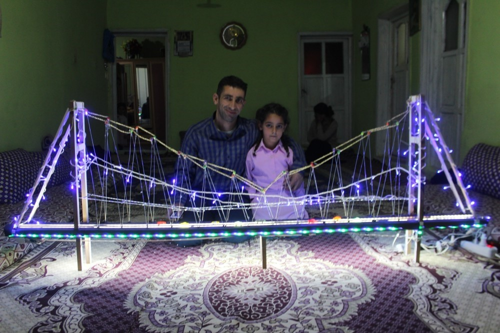 Yau011fmur Gu00fcder poses with the model bridge her father (left) built for her.