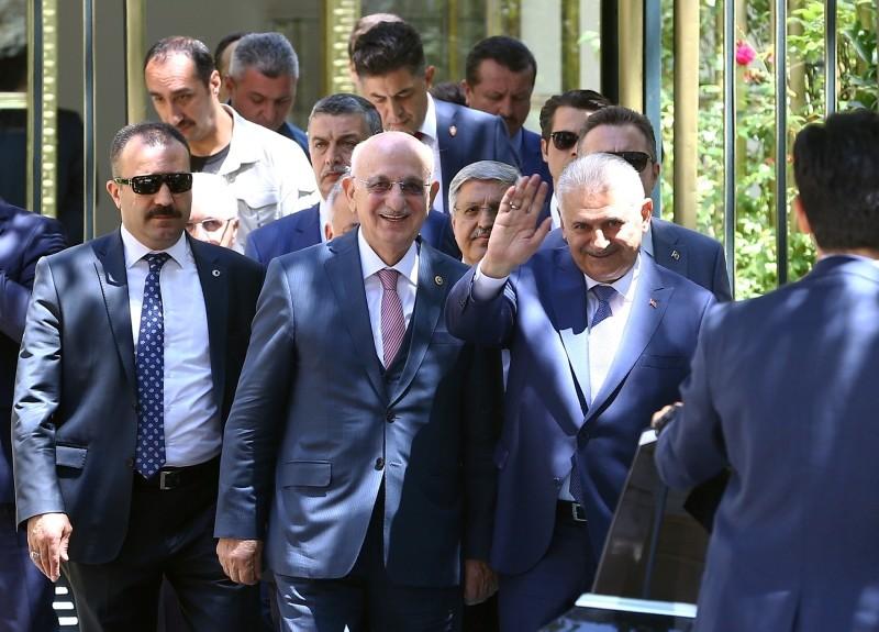 Prime minister Binali Yu0131ldu0131ru0131m waves to cameras as he leaves the Parliament alongside Speaker Ismail Kahraman (L), in Ankara, on July 3, 2018. (AA Photo)