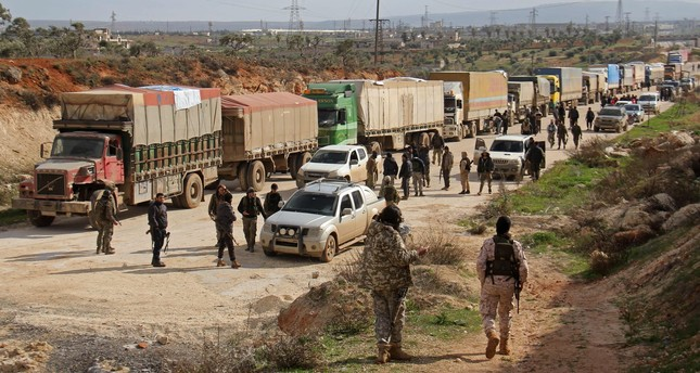 Opposition fighters and aid workers stand near a convoy of vehicles carrying United Nations food and medical aid on the outskirts of Kafraya. AFP Photo