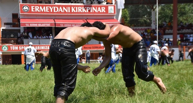 Two wrestlers try to put each other's back to the ground in one of many matches held on Friday in Kırkpınar, July 5, 2019.