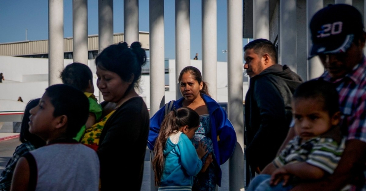 Migrants from Honduras wait in line at the Mexico-United States border crossing in Tijuana, Mexico on September 12, 2019 (AFP Photo)