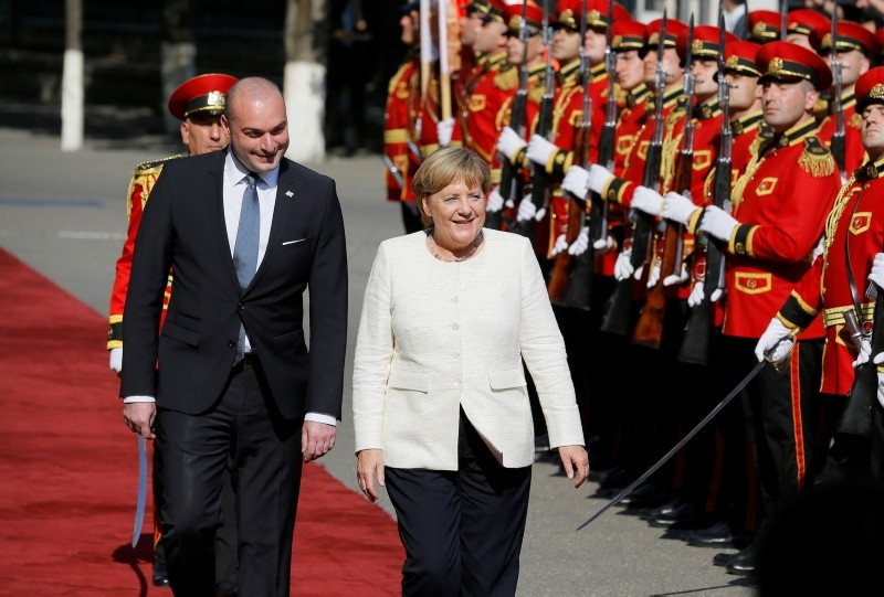 German Chancellor Angela Merkel (R) inspects a guard of honor with Georgian Prime Minister Mamuka Bakhtadze (L) during the official welcoming ceremony in Tbilisi, Georgia, 23 August 2018. (EPA Photo)
