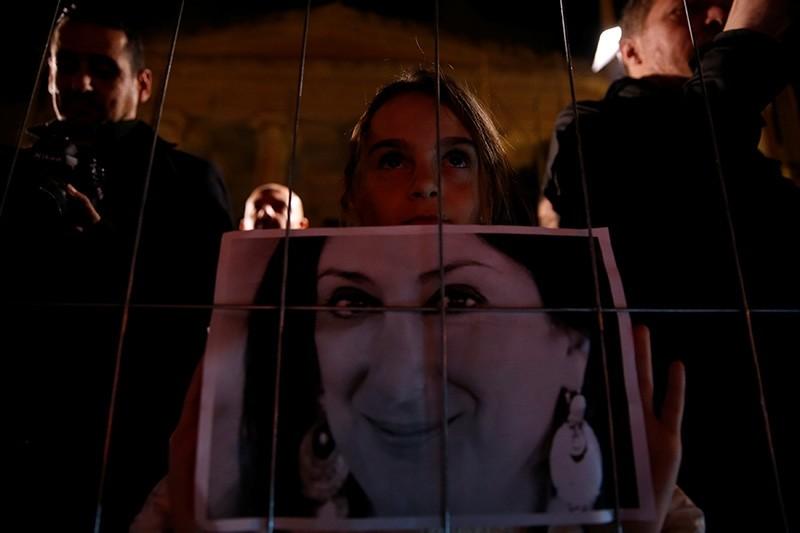 Girl holds photo of assassinated journalist Daphne Caruana Galizia near the newly rebuilt makeshift memorial during vigil to mark 13 months since her murder, in Valletta, Malta, Nov. 16, 2018. (Reuters Photo)
