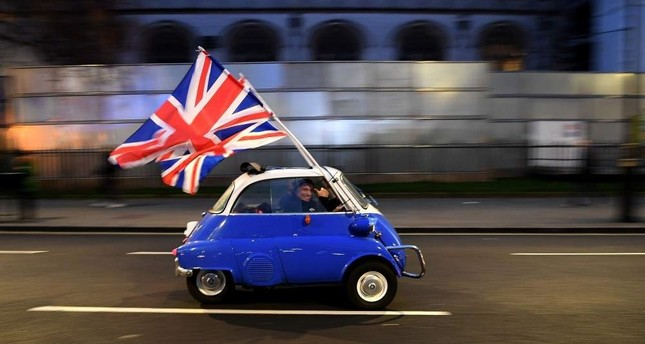 A man waves Union flags from a small car as he drives past Brexit supporters gathering in Parliament Square, central London, Jan. 31, 2020, the day that the U.K. formally left the EU. AFP Photo